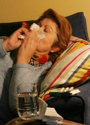 Una mujer se alivia los síntomas de la gripe