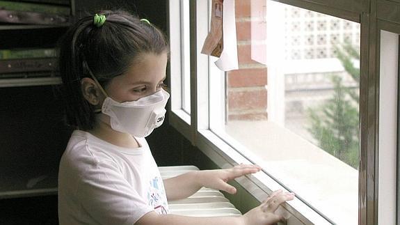 Niña con alergia se protege con una mascarilla para evitar en contacto con el polen. / R.I. Ideal