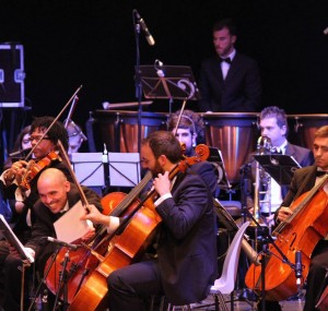 Pedro Domenéch, en primera fila, al violonchelo y Fernando Quiles, con la percusión al fondo, en el concierto sinfónico de APACHE